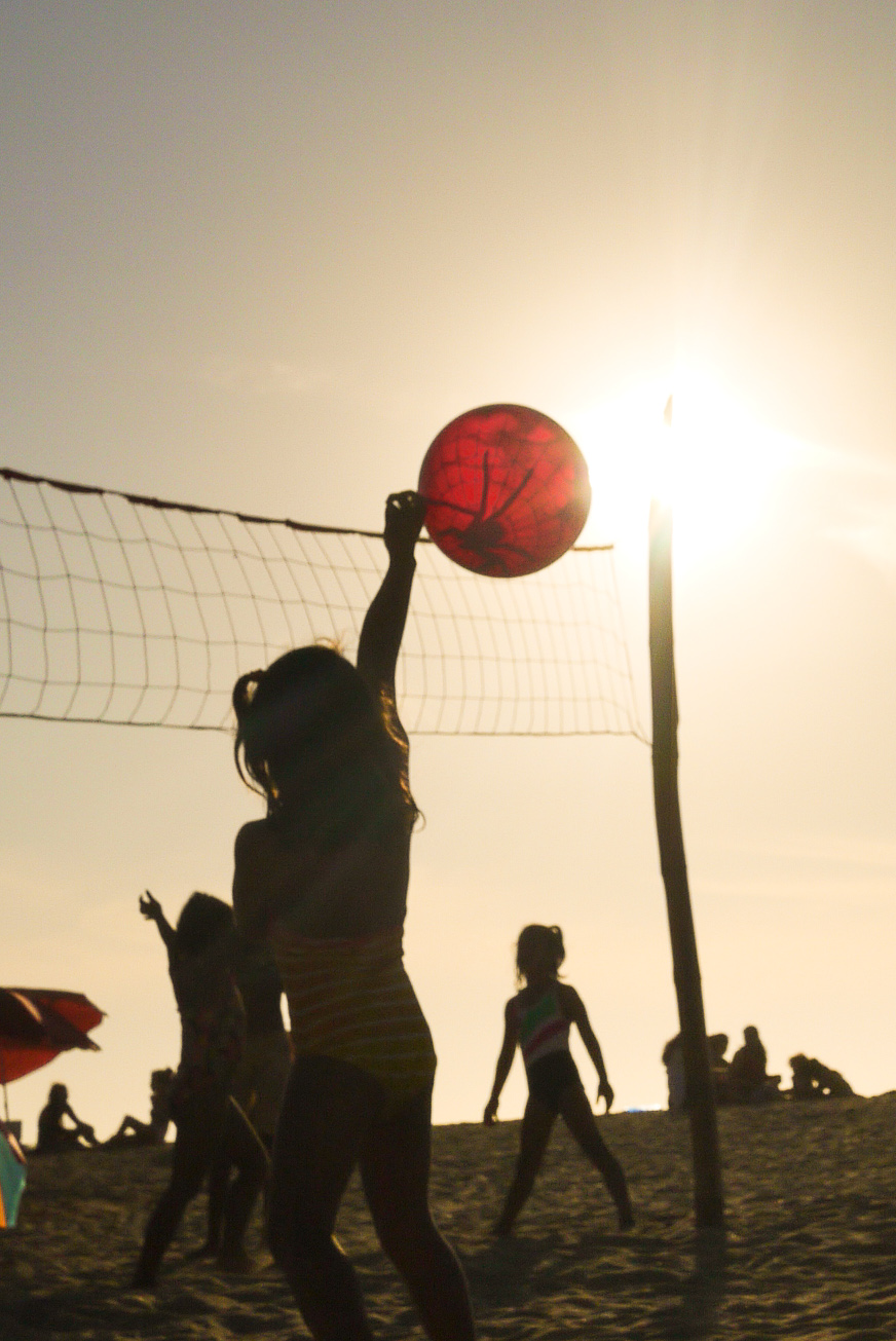 A young girl plays beach volleyball