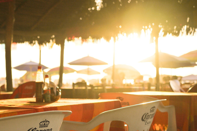 Sunset through a palapa on the beach.