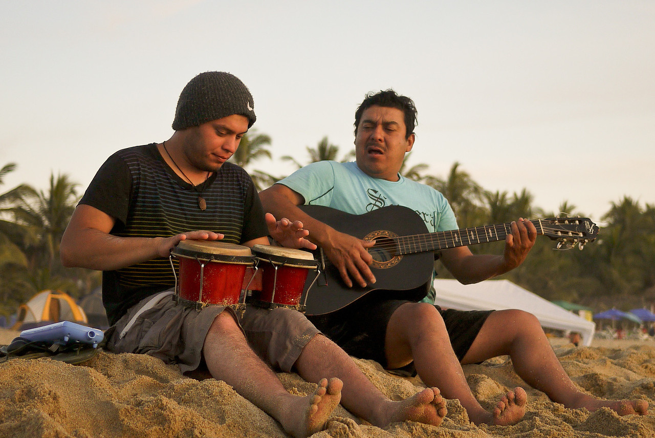Musicians on the beach at sunset.
