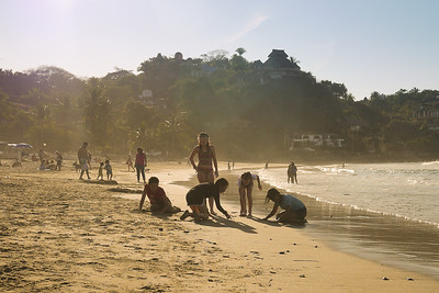 Sunset in Sayulita, Mexico as surfers catch the last waves of the evening and young children play in the sand.