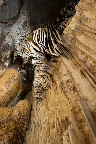 Stalactites and deeply fluted formations with tourquise waters of an unnamed Cenote near Merida, Yucatan, Mexico.