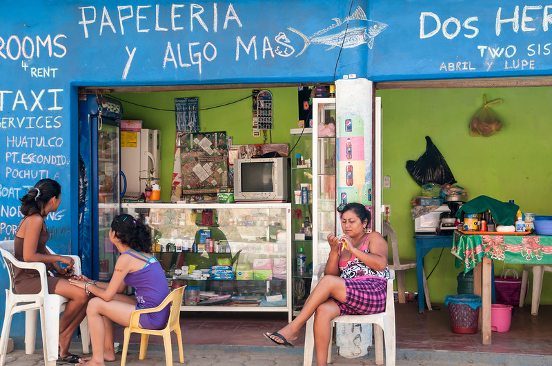 Women doing their nails in front of multi-service store, San Agustinillo, Mexico.
