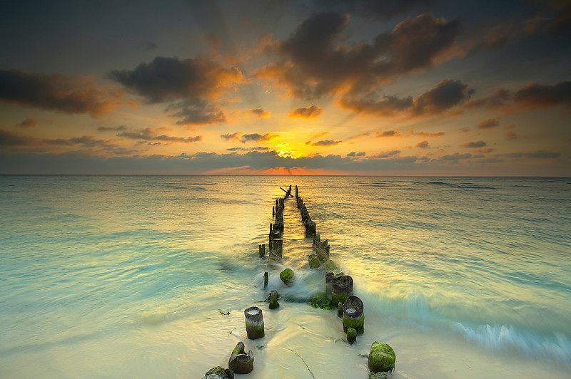 """A few days before I made this image, I noticed how the sun would soon be setting right behind this old eroded pier as the summer solstice approached.  So I returned to make a long exposure at sunset.  (See """"Exposed"""" on this page.)  Before that happened however, the light became quite dramatic so I went for a shorter exposure in order to show the light glistening on the water and lighting up the clouds.  It is good to arrive at a location with an open mind because you never know what to expect.  I try to see with an open mind and observe what elements attract the eye.  In post processing, this image had an overwhelming amount of color, so I had to de-saturate the sky in order to get back the details, which had become lost in blobs of bright orange."""