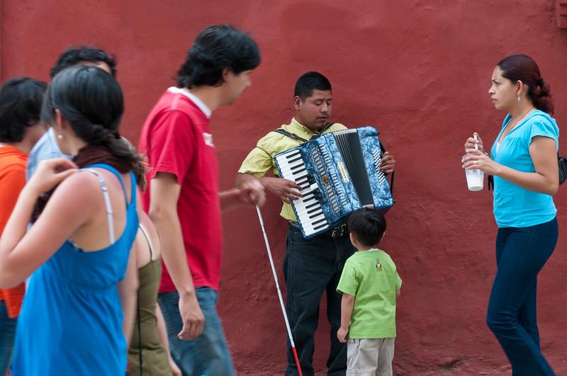 Pedestrians walk past blind accordion player, Oaxaca, Mexico.