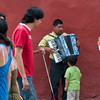 Pedestrians walk past blind accordion player, Oaxaca, Mexico.