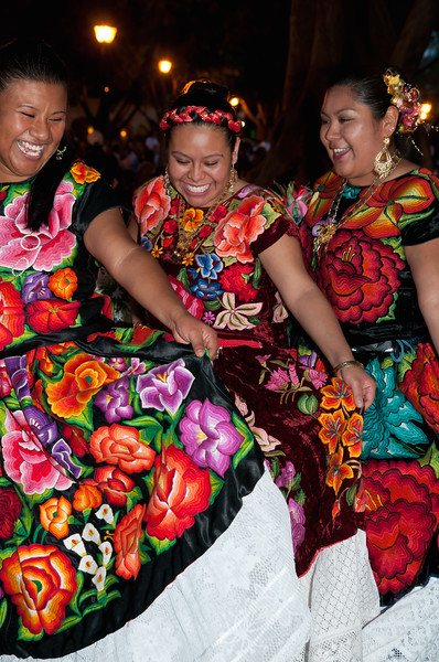Women show off their colorful dresses at a folk dance show, Oaxaca, Mexico.