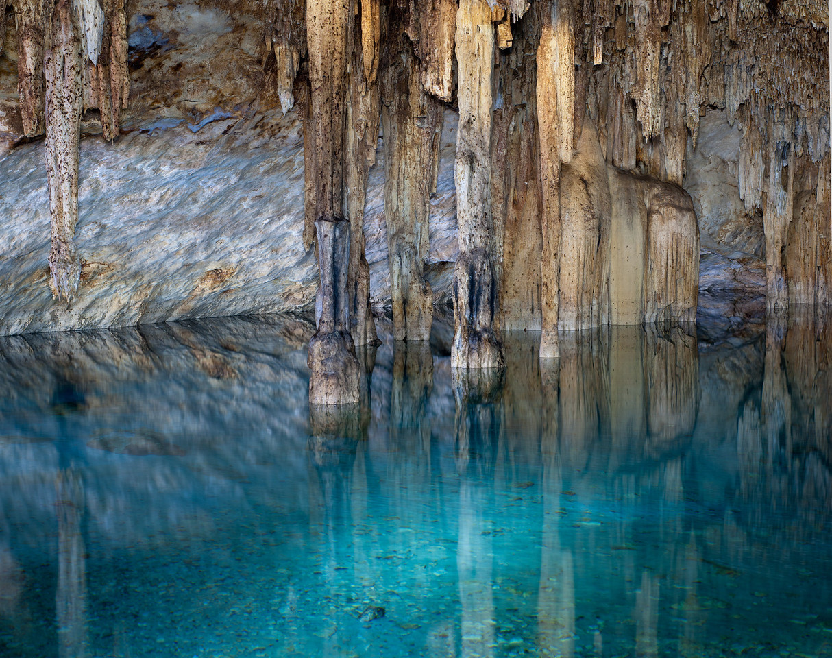 Stalagmites, and stalactites with tourquise waters of Cenote Papakal, near Merida, Yucatan, Mexico.