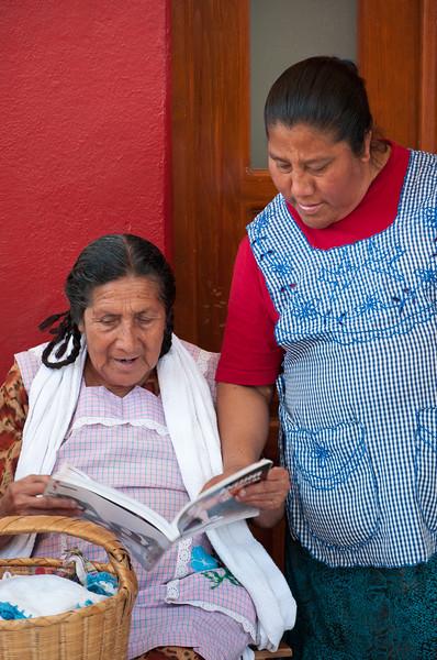 Women peruse shoe catalog at the Thursday market, Zaachila, Mexico.