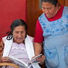 Women peruse shoe catalog at the Thursday market, Zaachila, Mexico.