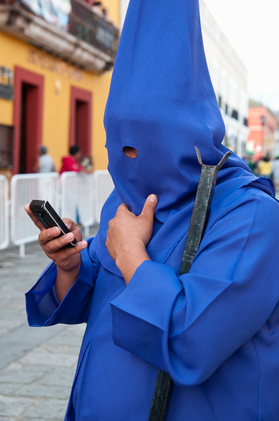 Hooded participant uses cell phone while waiting to march in the Procession of Silence held on Good Friday, Oaxaca, Mexico.