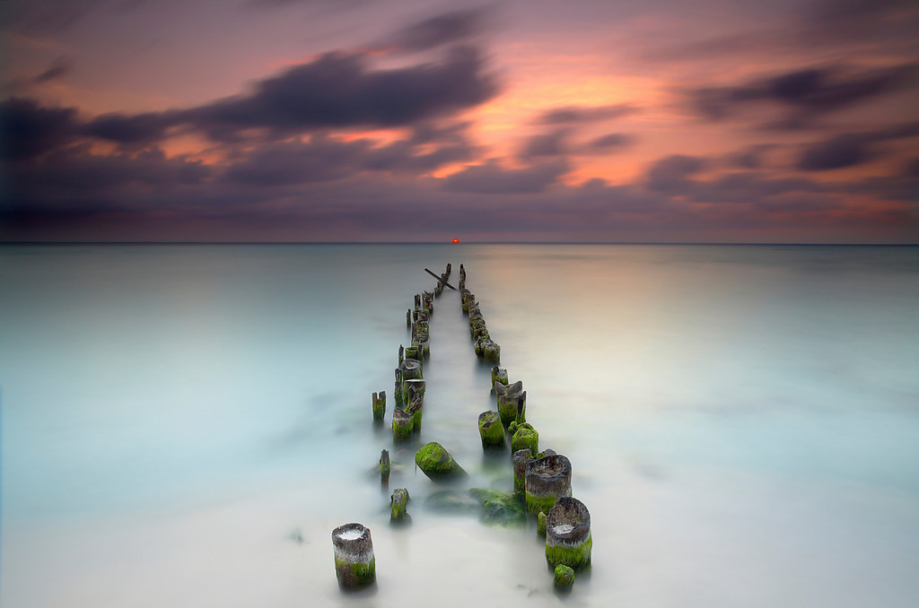 In October of 2005, Hurricane Wilma scored a direct hit on this island with category 5 winds gusting over  200 miles per hour. Many beaches were stripped of their sand, revealing old features not seen in many years, like this old pier on the north side of the island. I was told that before the hurricane, these pilings were under many feet of sand and that the beach used to extend well past the last post seen here. On the first day of my trip, the sun had set to the left of end of the pier, but I knew that over the next few days, the sun would move a little to the right each day.  (In landscape photography it pays to know how the natural world works, just as a bird photographer must know the habits of the birds to get the best shots.)  On the last day of my trip, the sun set right at the end of the pier.  I was ready and had an image in my head of what I hoped I could capture.  Fortunately the sun dropped below the clouds at the last minute and because visible right as the sun set.  I had taken photographs on the previous evenings just in case this evening turned out to be cloudy just to be on the safe side.