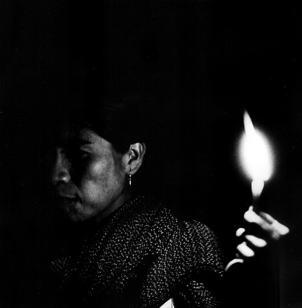 Maria Sabina's daughter holding a candle for her mother during a magic mushroom ceremony, Huautla de Jimenez, Oaxaca (ca 1972)
