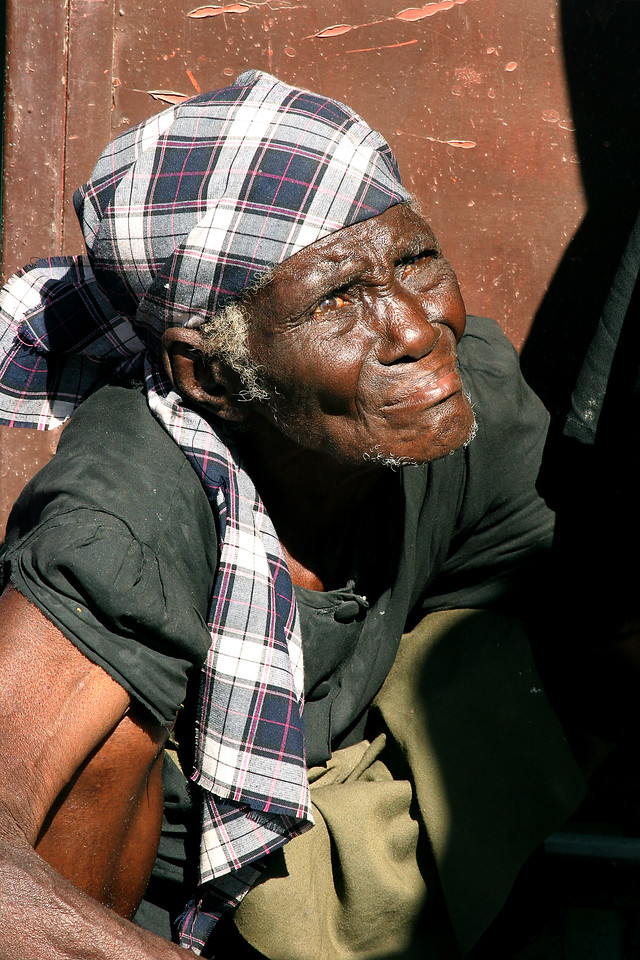 Cité Soleil, Haiti (Panetta)  A woman waits under the scorching sun to receive rice and a jug of water.