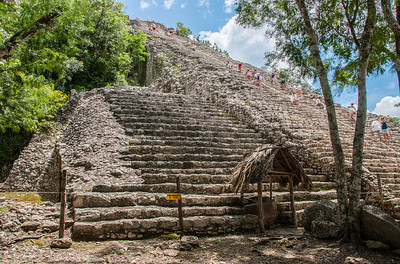 Tourists climbing up the Mayan ruins in Mexico