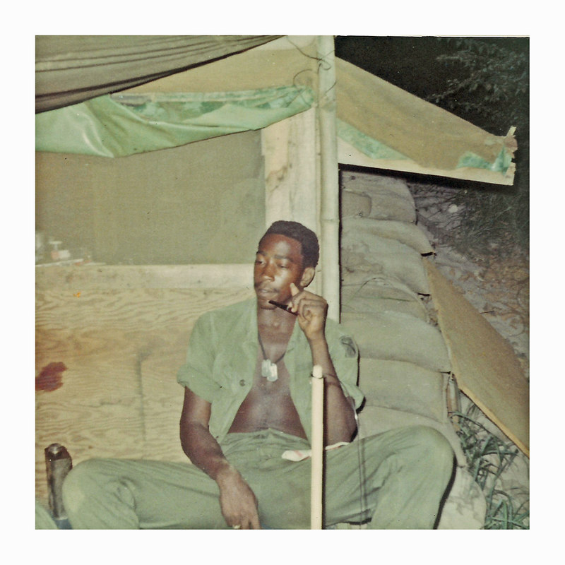 """JM24: A grunt, reported to be Jake L. """"Snake"""" Atkins of the weapons platoon and rear-area supply, enjoys pipe smoking outside his tent at night. Note his dogtags, and the sides of the barracks are raised to let in some air."""