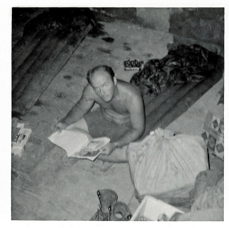 JM99: James M. 'Buddy' Prust sits on his air mattress on the floor of his bunker, reading. Prust passed away after Vietnam from natural causes.