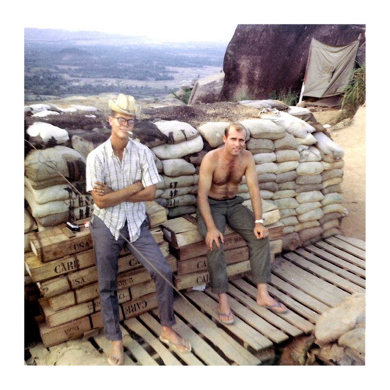 JM46: At a firebase camp are Jim Turner (TX) and Norman Walter. Is that a poncho stretcher leaning against the big rock? The boxes say CARE on them
