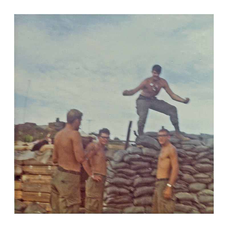 "JM63: L to R: Howard C. Tomlin, ""Poncho"", Richard Smith (KS) acts like Tarzan on some sandbags and Willard D. Anderson (TX)"