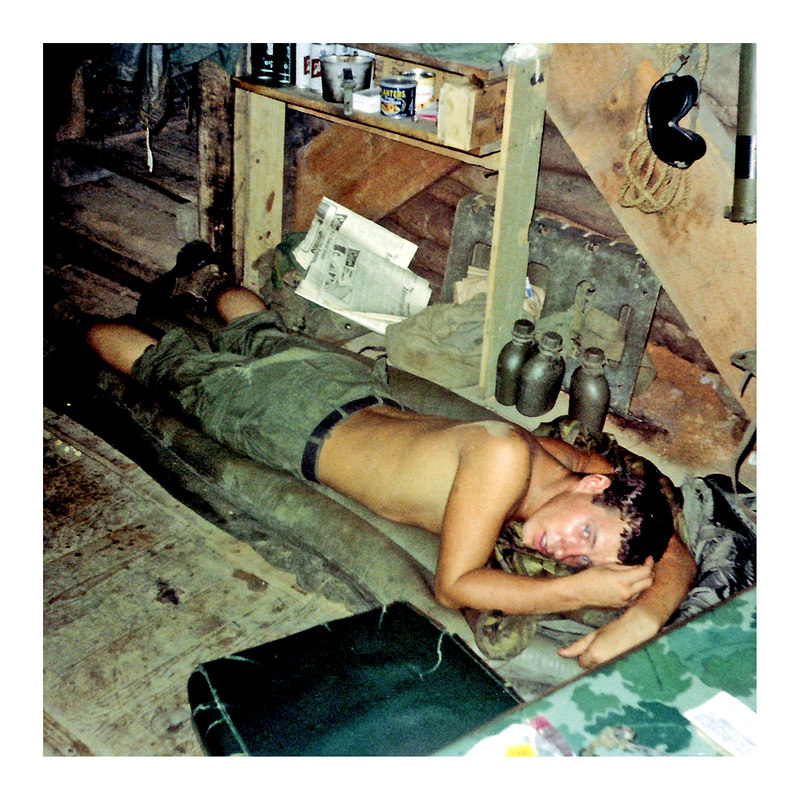 JM18: Mike Bonk (OH), 4th Platoon,  trys to nap on his air mattress on the floor of a bunker. Note the Peanuts, goggles, LAW, canteens, and Schlitz