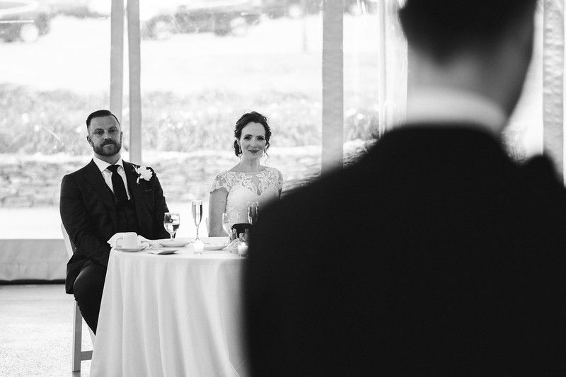 The bride and groom smile as they watch the Mike of Honor give a speech.