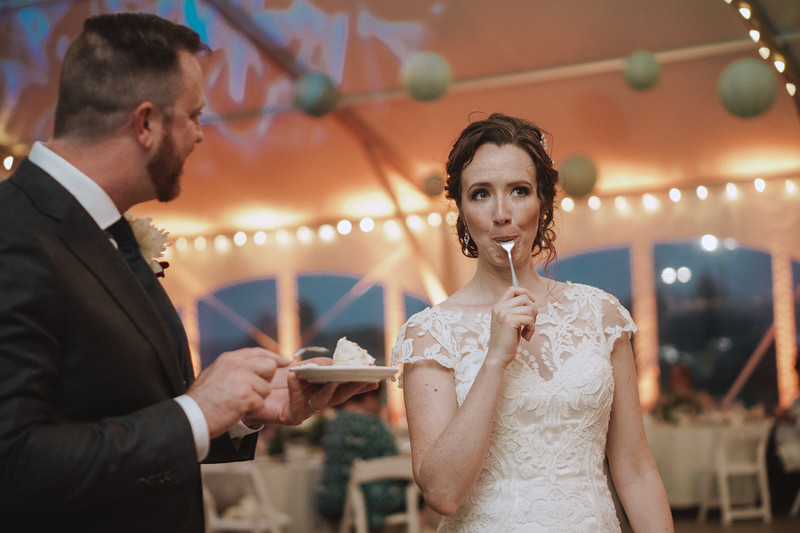 The groom watches as the bride makes a funny face while pulling the fork out from between her lips.