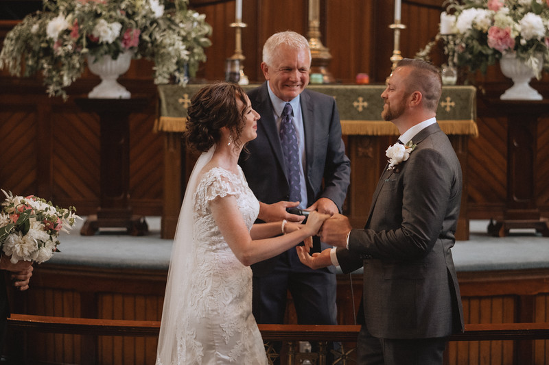 The bride and groom, hand in hand, facing each other and beaming while the reverend smiles in the background.