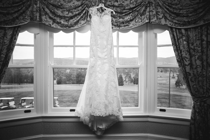 Wedding dress hanging in a window.
