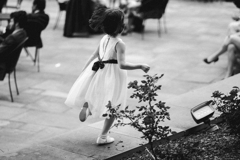 A flower girl sprints along a wall at the cocktail hour.