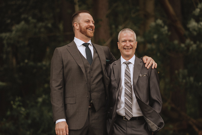 The groom and his groomsman laughing, each with an arm around the other, in the woods.