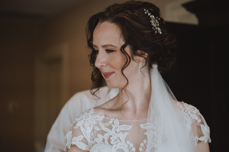 Bride smiling over her shoulder as her Mike of Honor buttons her dress.