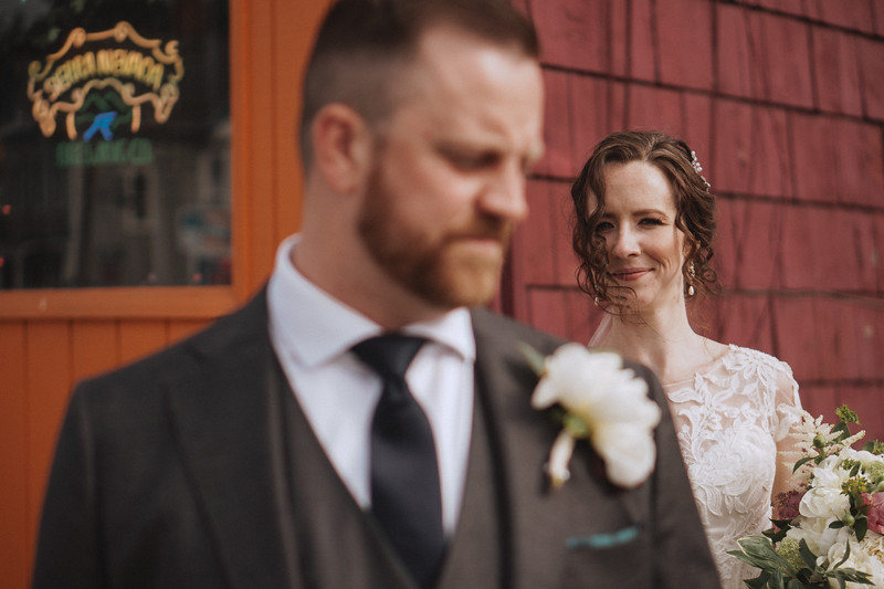 The bride looks over the grooms shoulder outside of the bar.