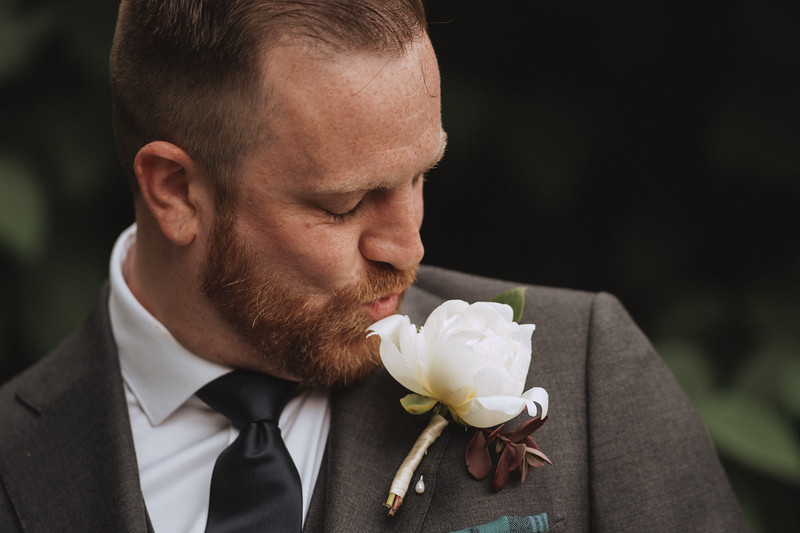 The groom playfully kissing the large white flower boutonniere pinned to his lapel.