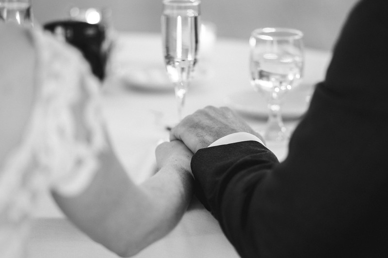 The bride and groom hold one another's hands on the table.