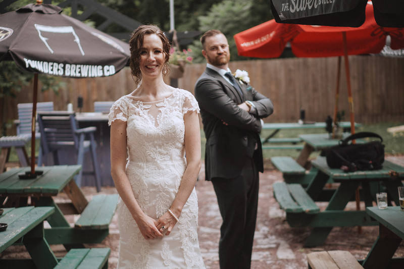 The bride smiles into the camera innocently as the groom, arms folded, checks her out from behind.