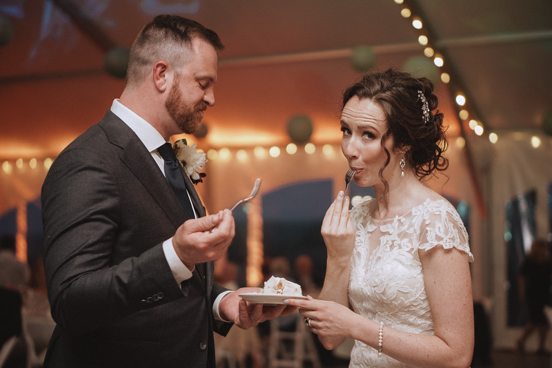 The bride pulls the fork slowly from her mouth as she raises her eyebrows at the camera and the groom is clearly considering something.