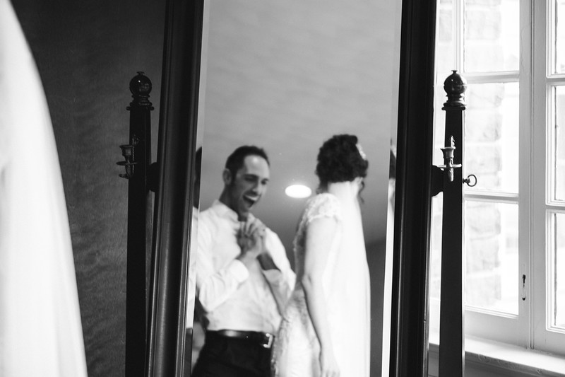 The Mike of Honor laughing with joy as he sees the bride completely in her dress, as reflected in a mirror.