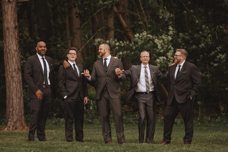 The groom and his friends joking around in a wooded area.