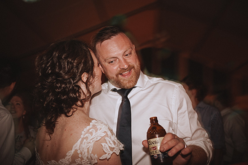 The bride whispers in the grooms ear as he grins and holds a beer.