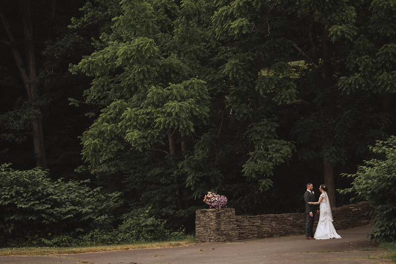 The bride and groom talking to each other at the bottom of a stone bridge, under a canopy of trees.