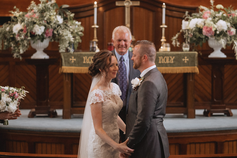 The bride and groom, holding hands and smiling in front of the alter.