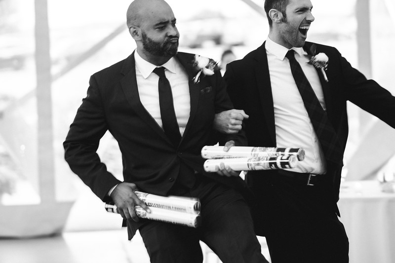 The Mike of Honor and a groomsman dance into the reception holding confetti canons like guns.
