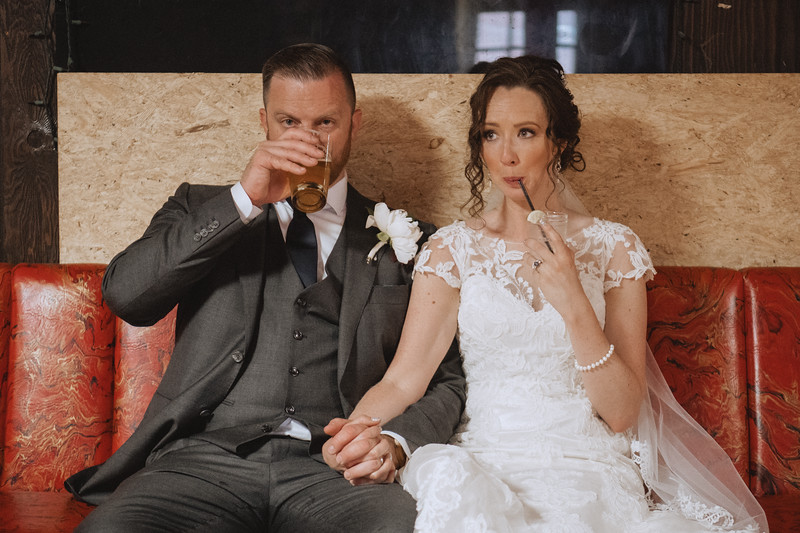 The groom sips his beer while the bride drinks her cocktail through a straw and they both make faces as if they are bored, but in a funny and ironic way.