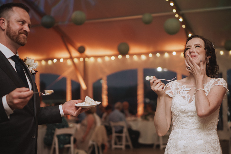 The bride laughs as she wipes frosting from her lips and backs away from the groom who holding cake and a fork and looks to be up to no good.