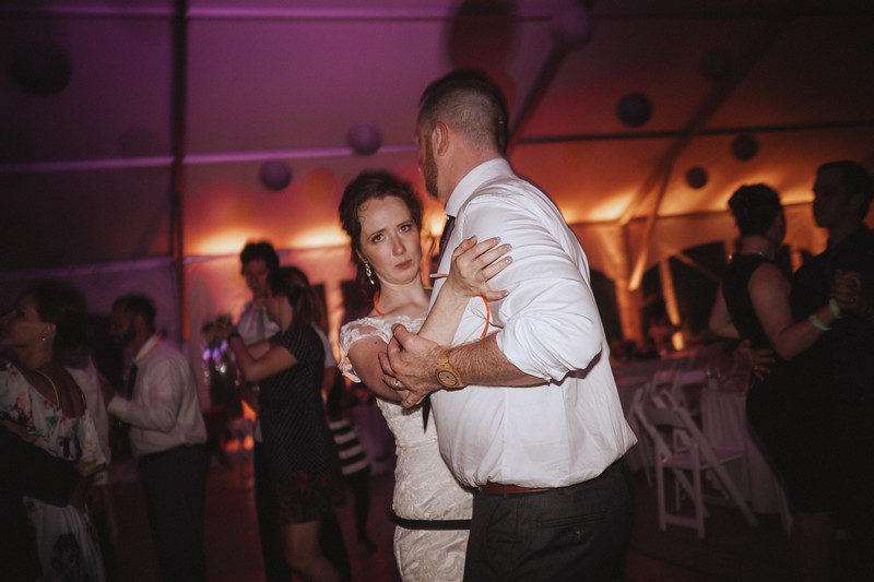 The bride makes a funny face as she dances with the groom.