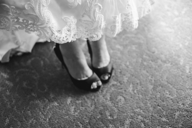 The lace rimmed bottom of the bride's dress revealing her heels against a swirly patterned carpet.