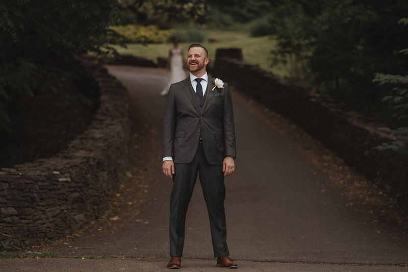 The groom laughing as the bride walks up behind him, down a long path with stone stacked walls, under a canopy of trees.