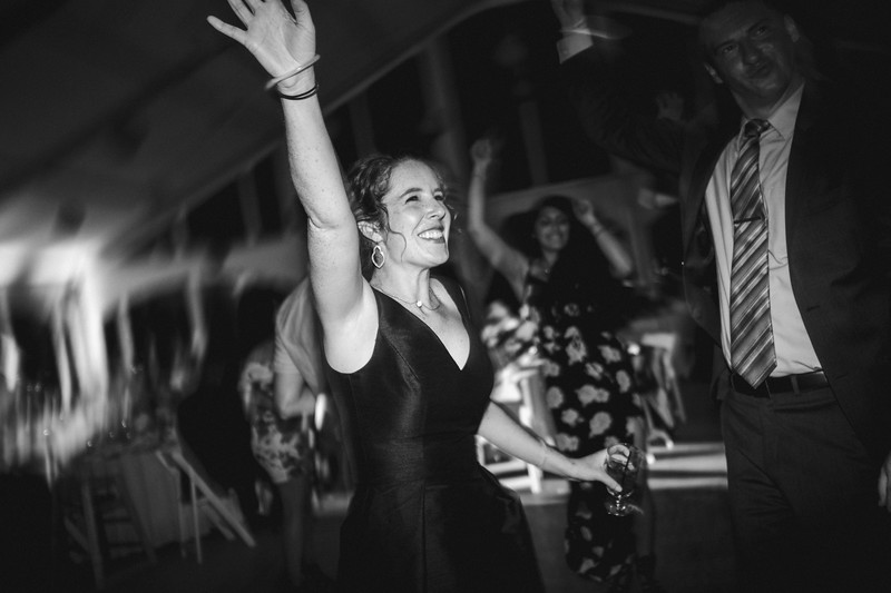The bride's sister dances with her arm waving in the air and a big smile on her face.