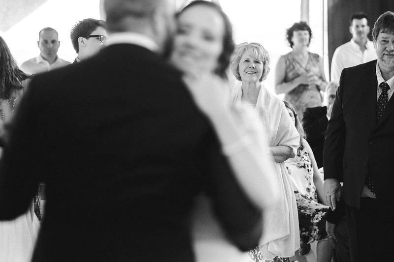 The bride's mother watches smiling from the background as the bride dances with her head on the grooms shoulder.