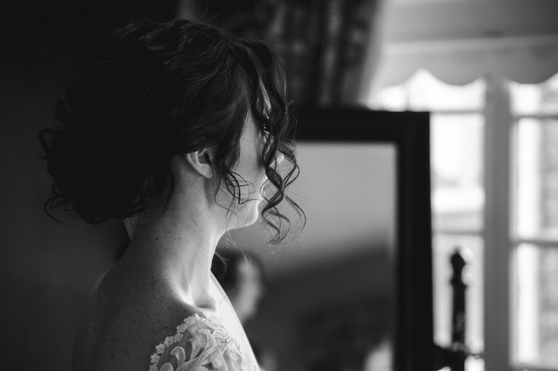 Bride gazing through a window.