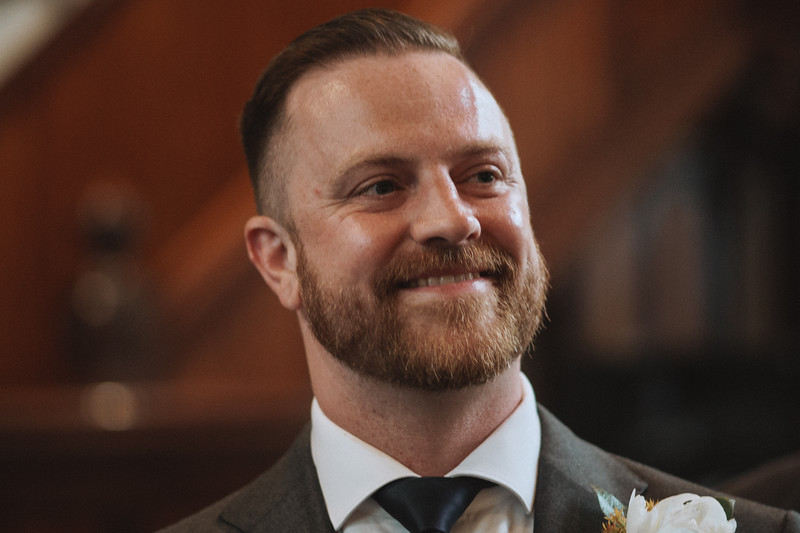 The groom smiling as he see's his bride.